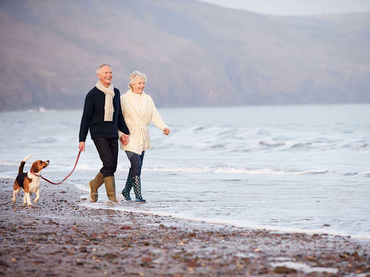 Happy retired couple dog walking on the beach