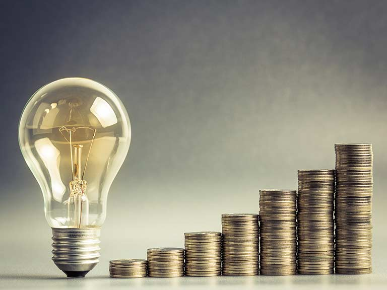 A lightbulb stands next to increasing piles of money to symbolise rising energy costs