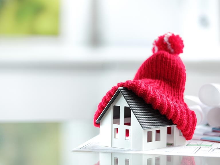 Model of a house with a woolly hat on the roof