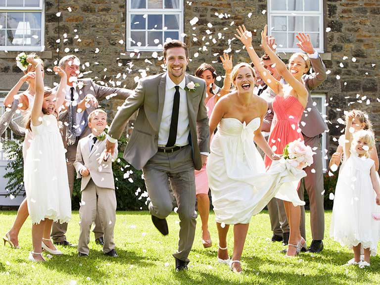 Guests showering wedding couple with confetti