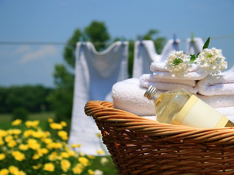 Basket of clean towels and washing online in the garden
