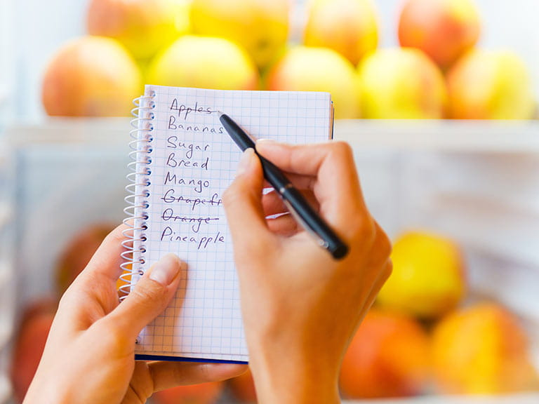 Woman crossing groceries off of shopping list