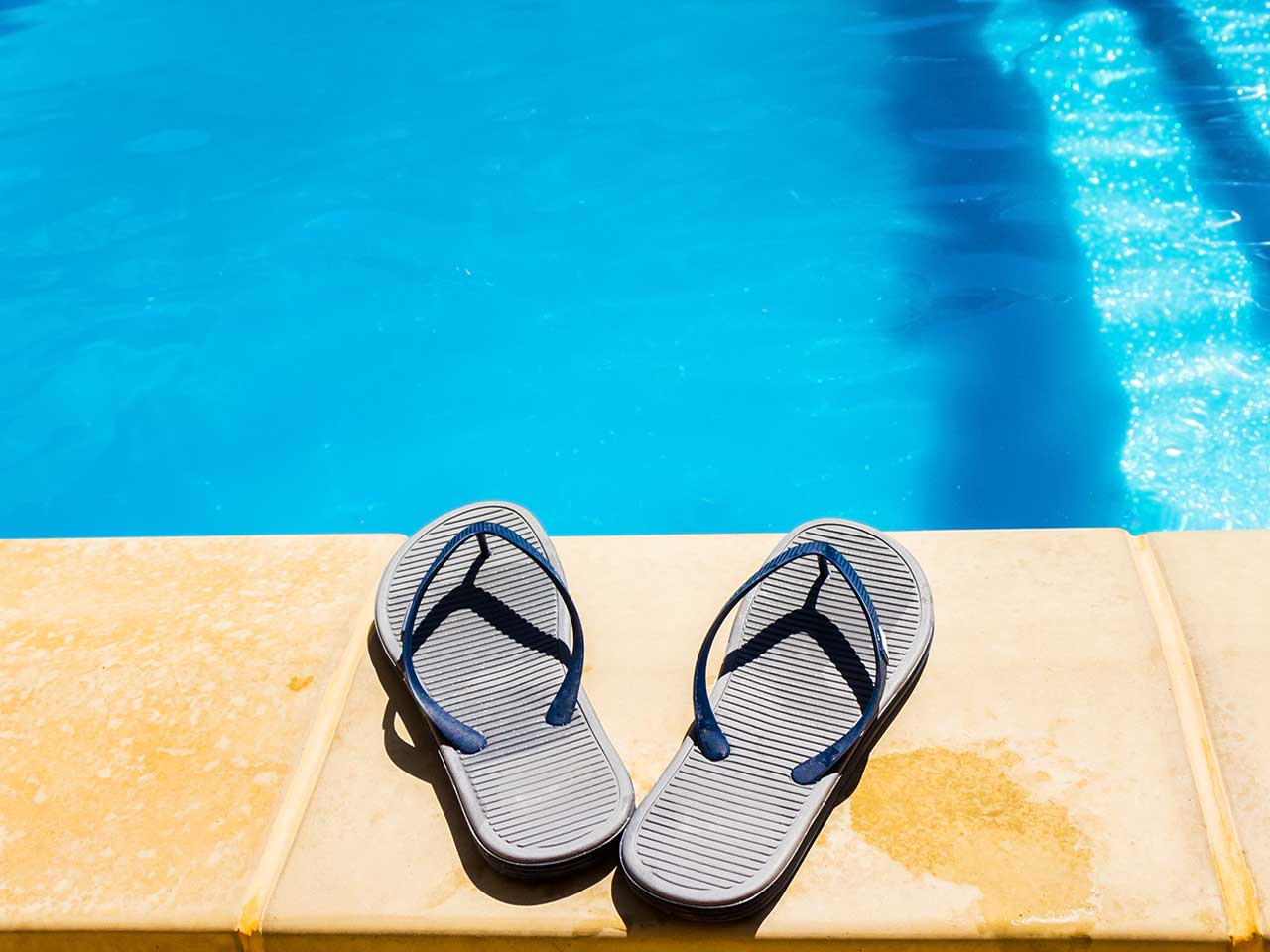 Flip flop shoes by a swimming pool