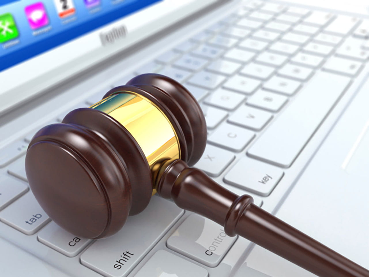Auction gavel resting on a laptop