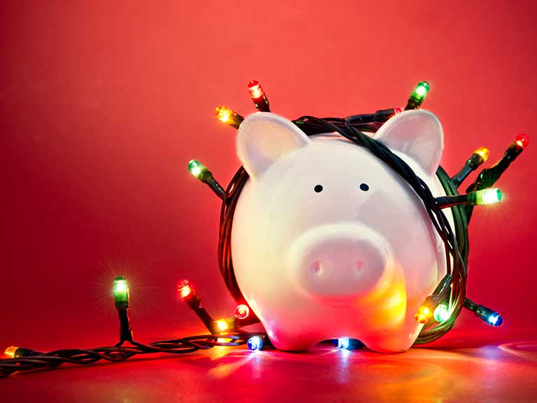 A piggy bank wrapped in Christmas lights to represent the cost of Christmas
