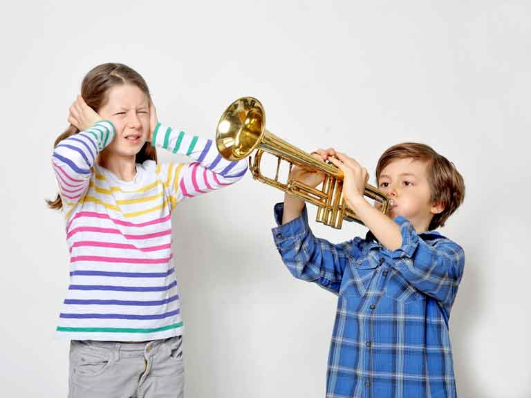 Boy playing trumpet while girl puts her hands over her ears to block out the noise