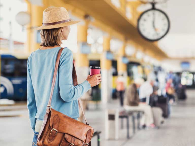 Woman in coach station holding a coffee