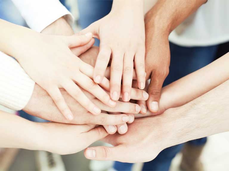 Hands joined to show unity, team work and equality