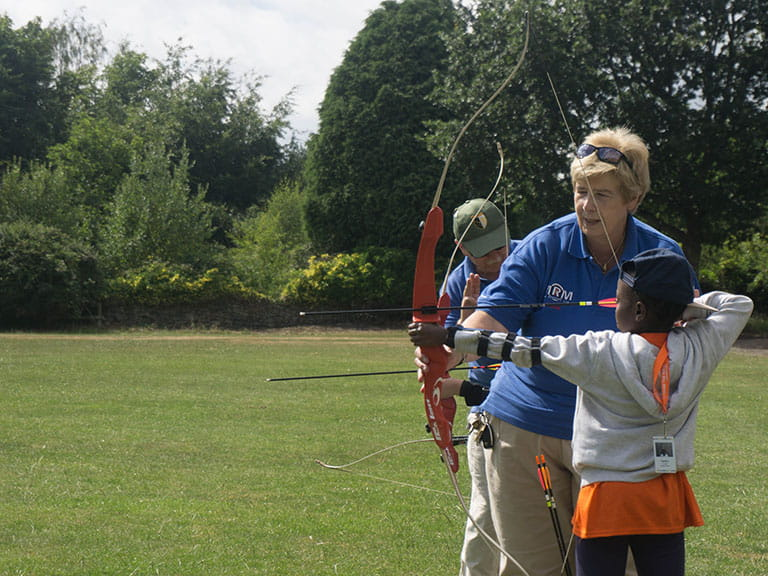 A volunteer teaches a child archery