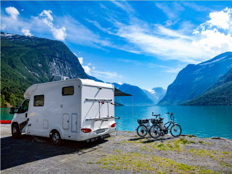 Motorhome and two bicycles parked next to Norwegian fjord