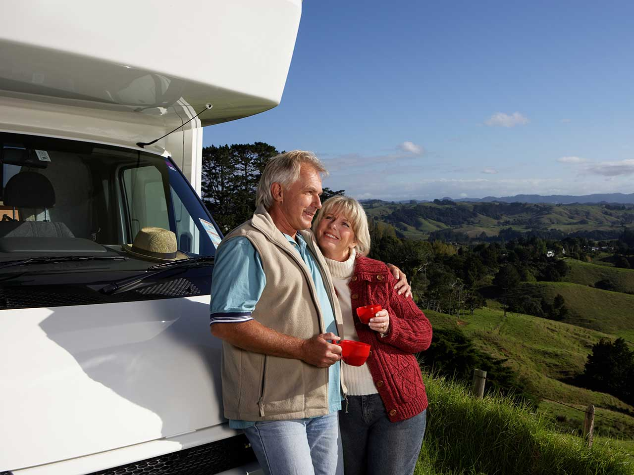 Mature couple leaning on a motorhome