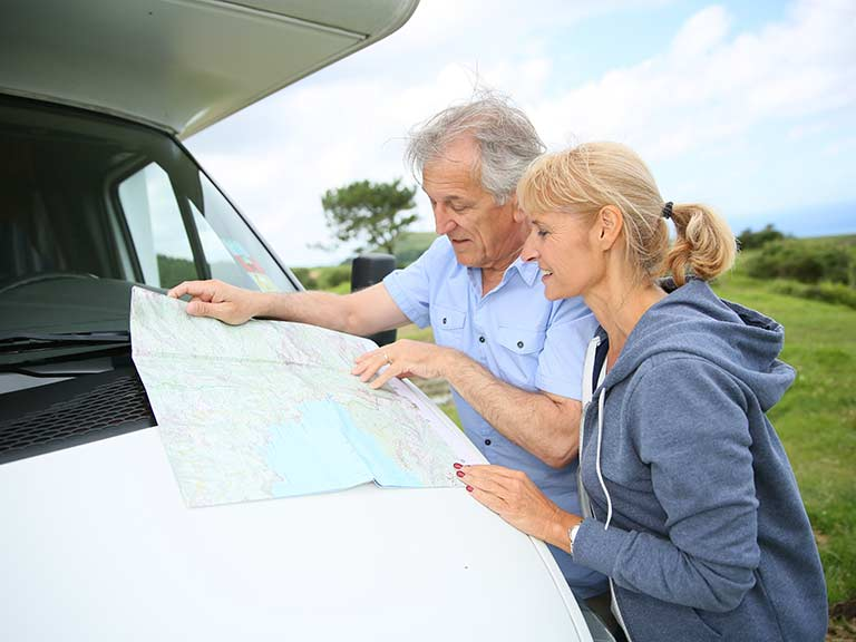 An older couple plan the route of their motorhome holiday to save money