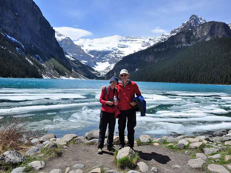 Couple standing by a beautiful lake and mountains in Canada.