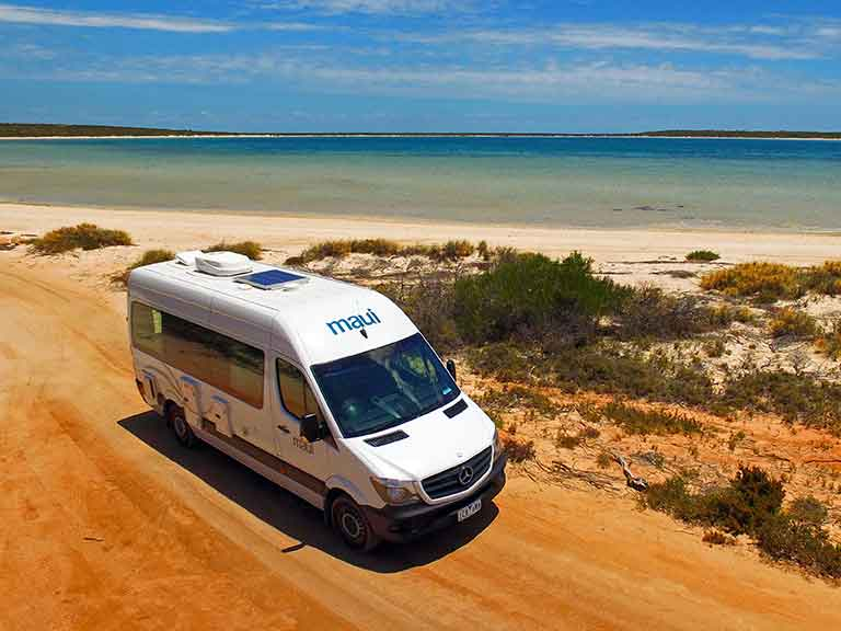 Motorhome parked by a white sandy beach in Western Australia.