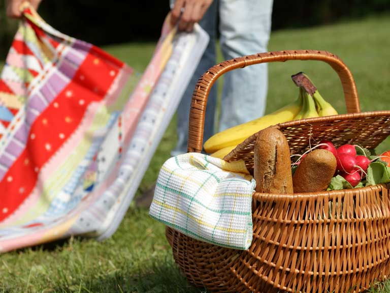 Man unfolding picnic blanket on grass next to a basket filled with food.