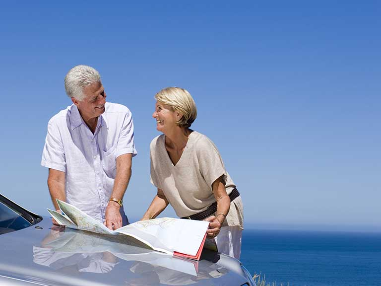 An older couple consult a map during their drive