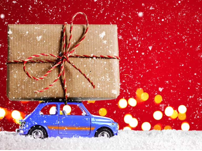 toy car with large gift wrapped parcel tied to the roof of the car driving