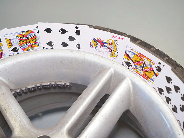 Playing cards in a car wheel to keep the tyres clean when painting the alloys