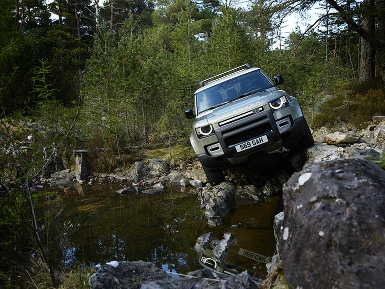 New Land Rover Defender on rocks by lake