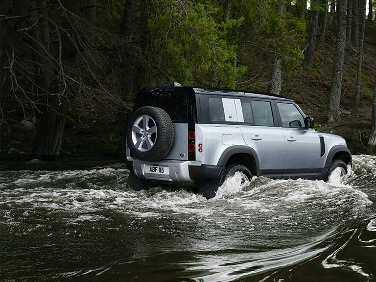 All new Land Rover Defender driving through a river