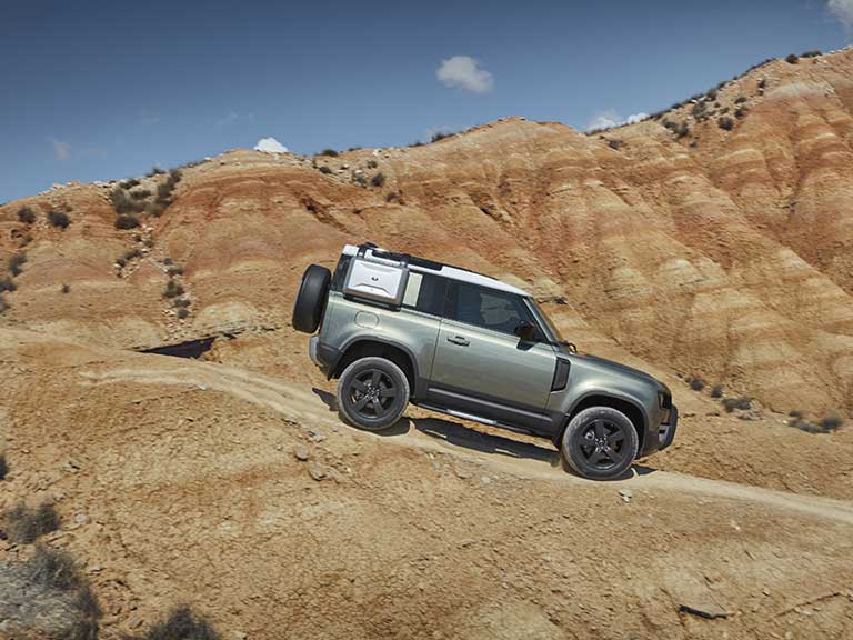 New Land Rover Defender driving in a canyon