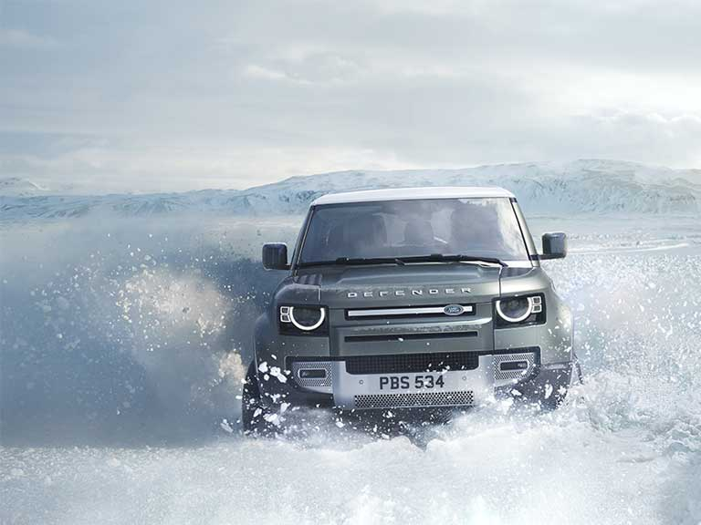New Land Rover Defender driving through a snow drift