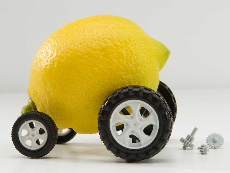 Lemon on wheels to represent buying a dodgy or shoddy car