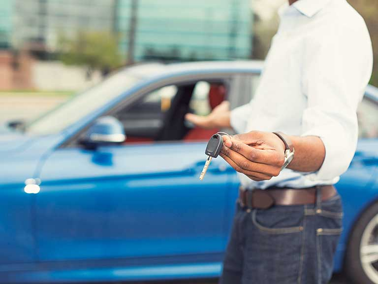A car salesman hands over the keys to a car bought via a PCP