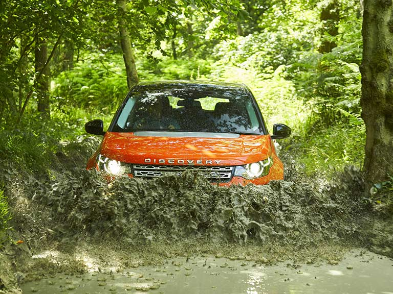 Land Rover Discovery Sport driving through mud