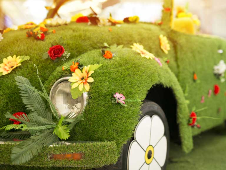 Car covered in artificial grass and flowers