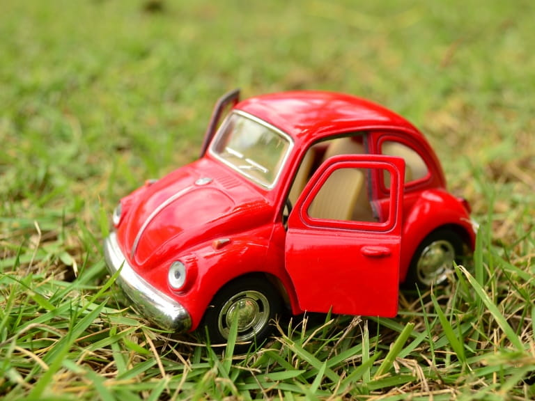 A red toy car on the grass to represent downsizing to a smaller car