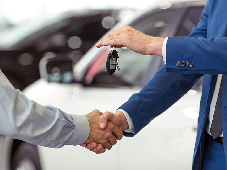 Two people shake hands after selling a car