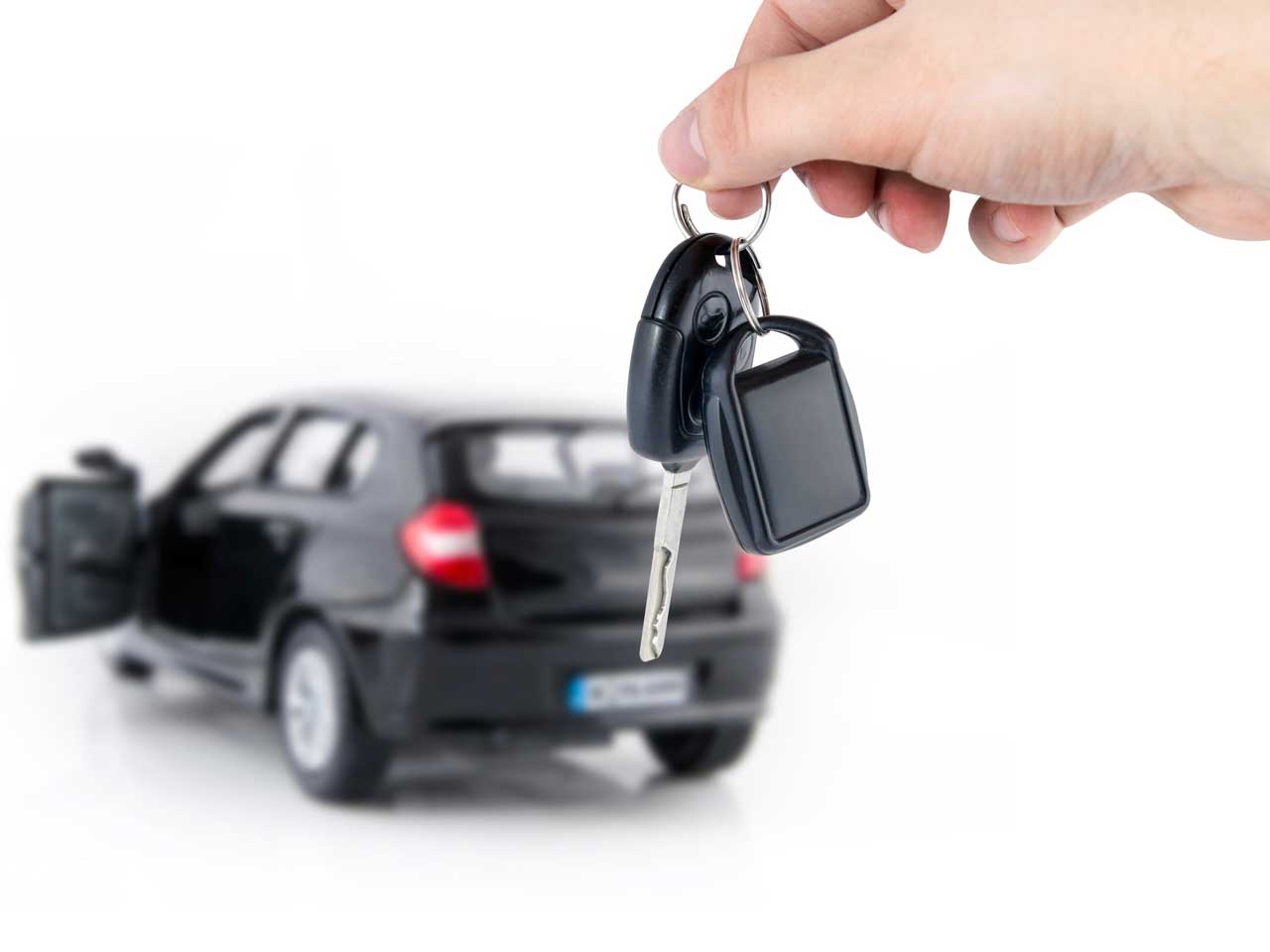 Person holding car keys in front of a car to represent buying or selling a car