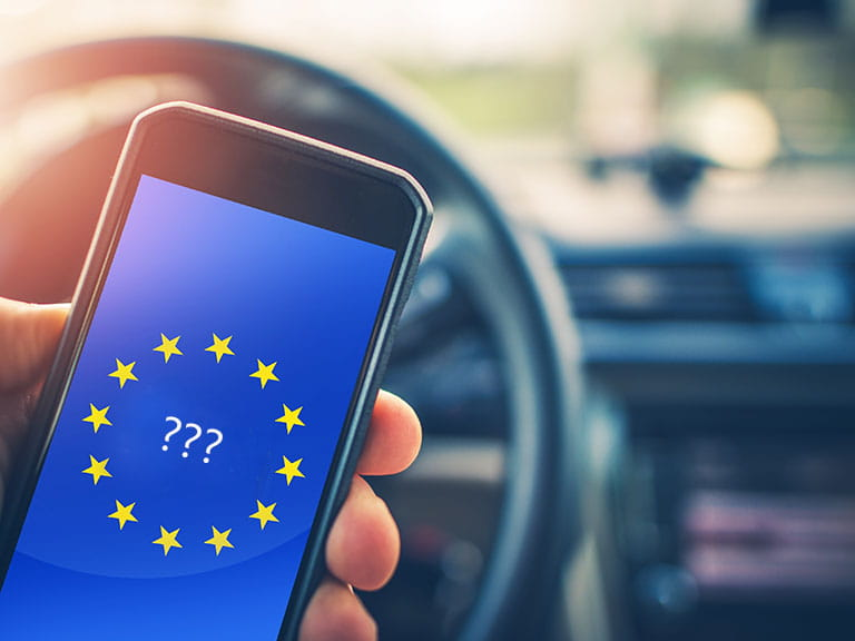 Question marks and the EU flag in a car on a phone display to represent how Brexit might affect your driving licence