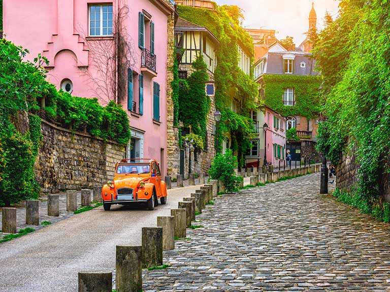 An old car drives through the streets in Montmartre in Paris, France