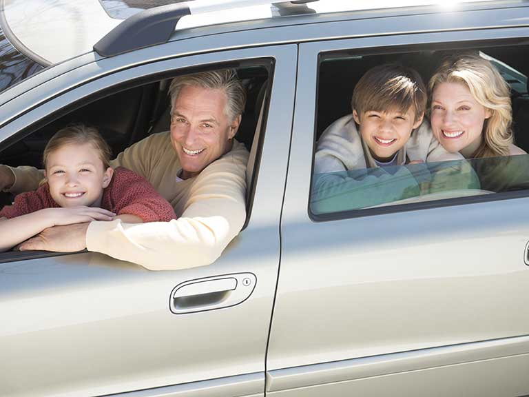 A family in a car, smiling because they are not bored