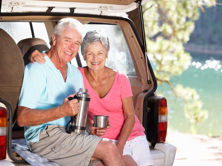 Couple drinking from a flask outside their car to represent travelling and road trip