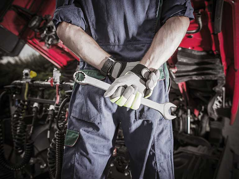 A mechanic stands holding a wrench