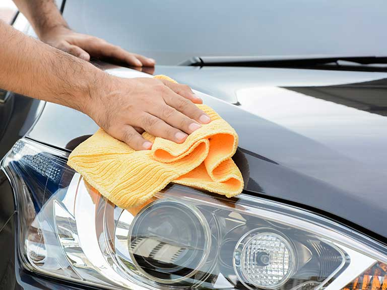A man cleans a mark from his new secondhand car