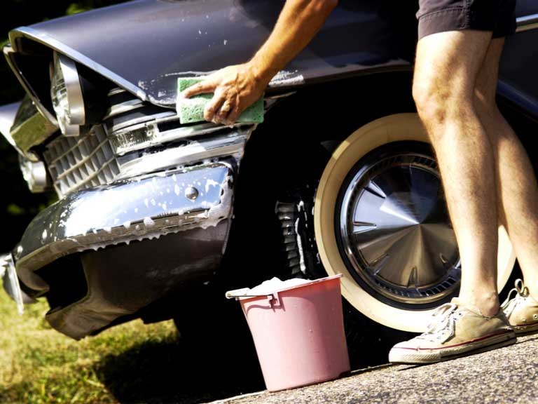 Man washing classic car with sponge and soapy water