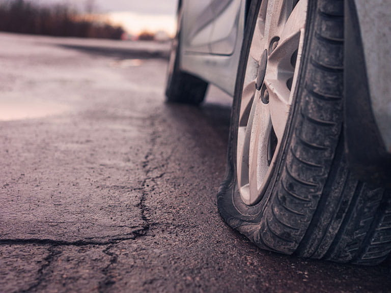 A car with a flat tyre stopped on the side of the raod