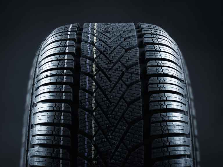Single new car tyre showing deep tread