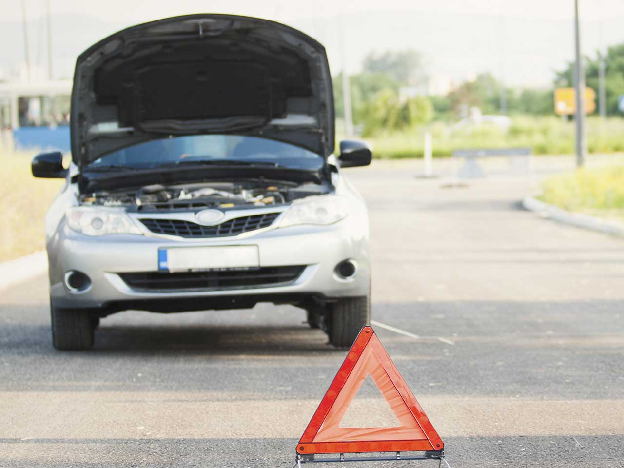Broken down car with bonnet raised and emergency triangle laid out on the road ahead of the vehicle.