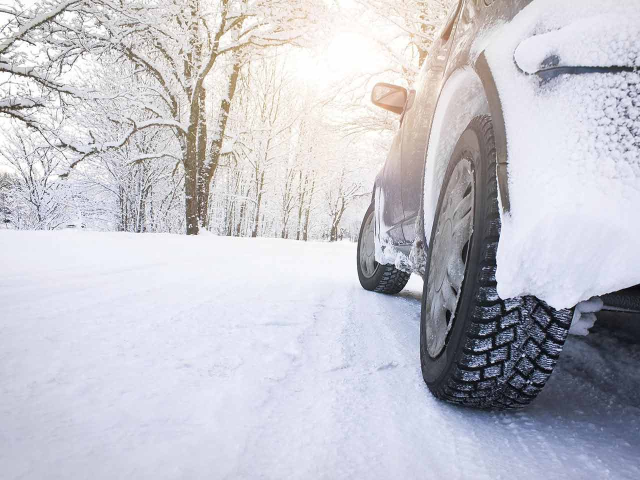 Car tyre against a winter road backdrop