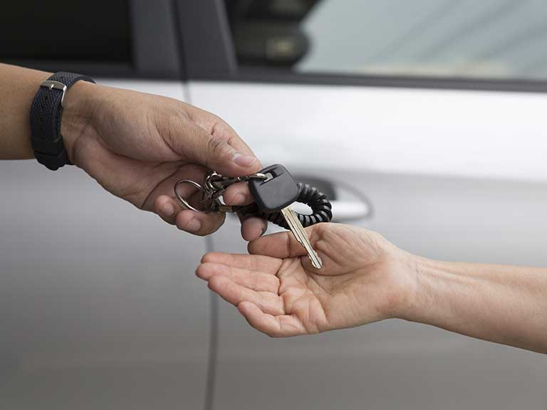 Handing over car keys to represent a car owner donating the car to charity