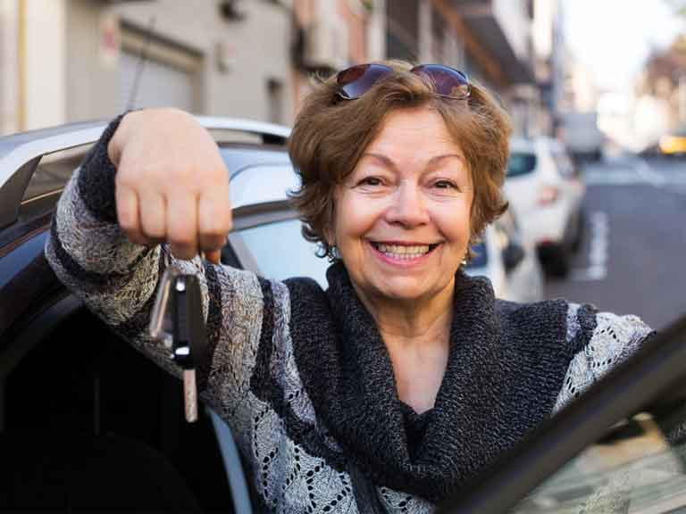 Older lady driver holding car keys next to car