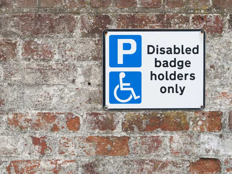 Disabled parking space sign on brick wall