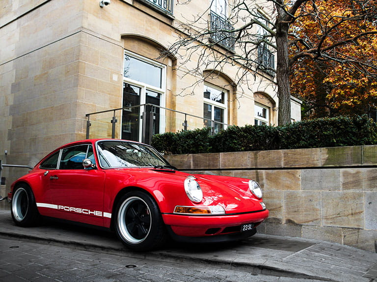 A red Porsche parked on the pavement