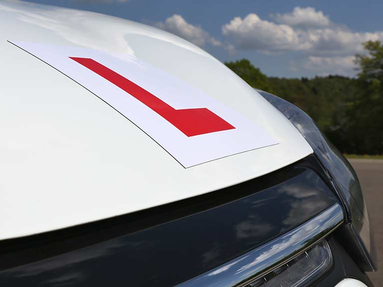 A red L plate sits on a car's bonnet