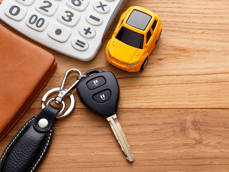 Car keys next to a calculator to represent the cost of hiring a car
